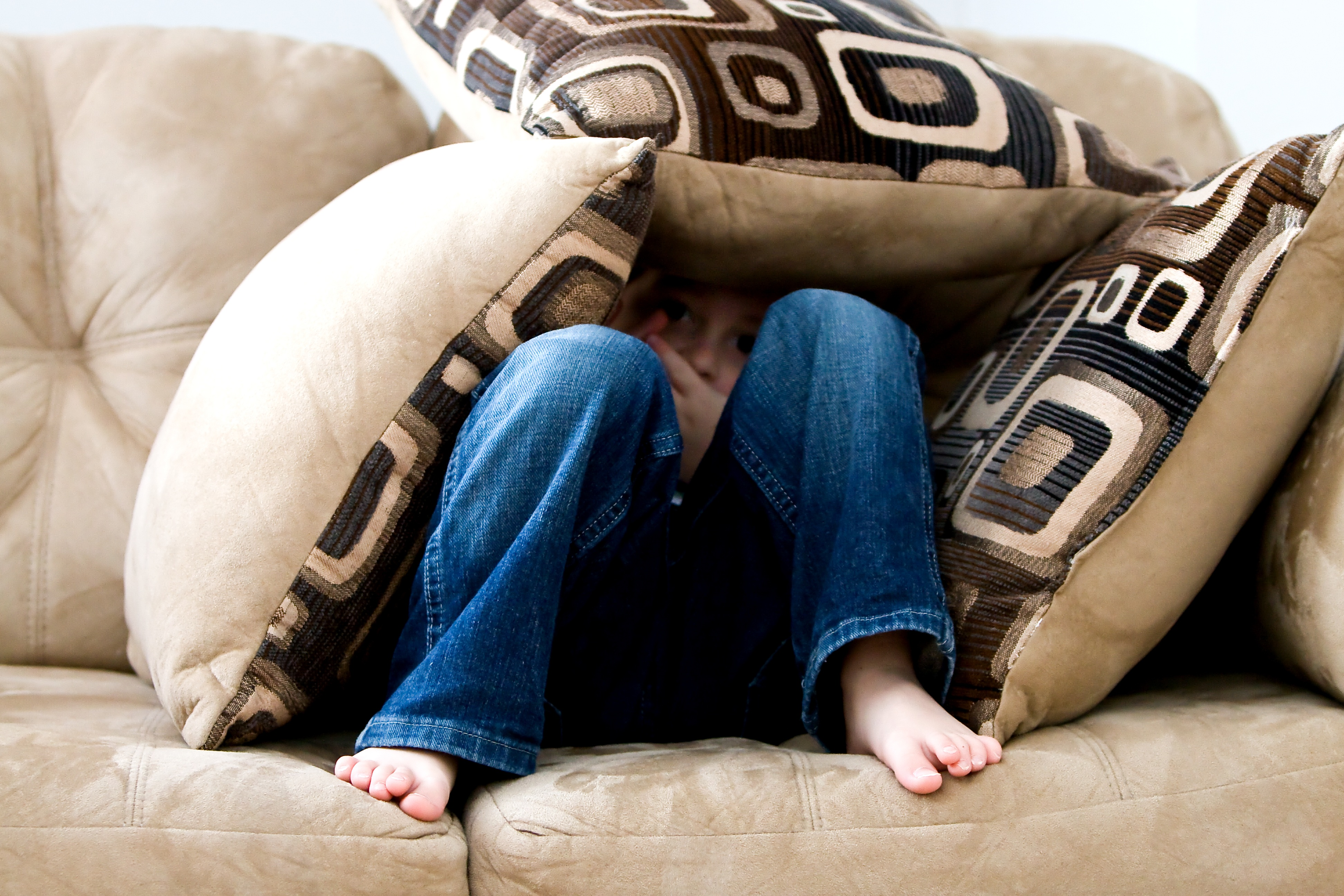 sitting on sofa with pillows over head