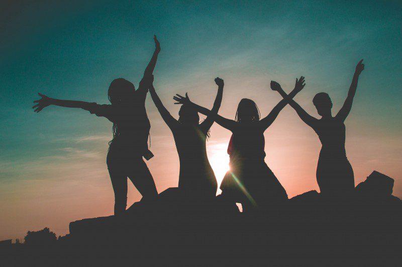 silhouette of ladies raising hands