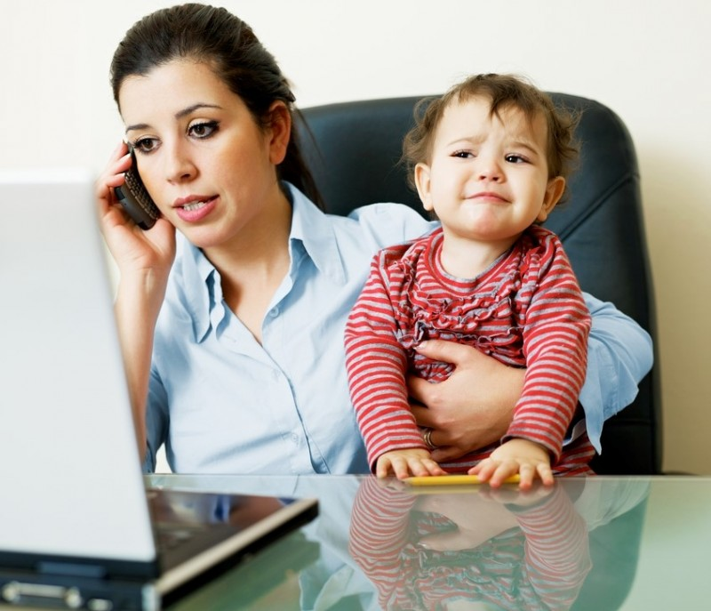Woman holds a struggling, frowning toddler while talking on the phone and working on her laptop.