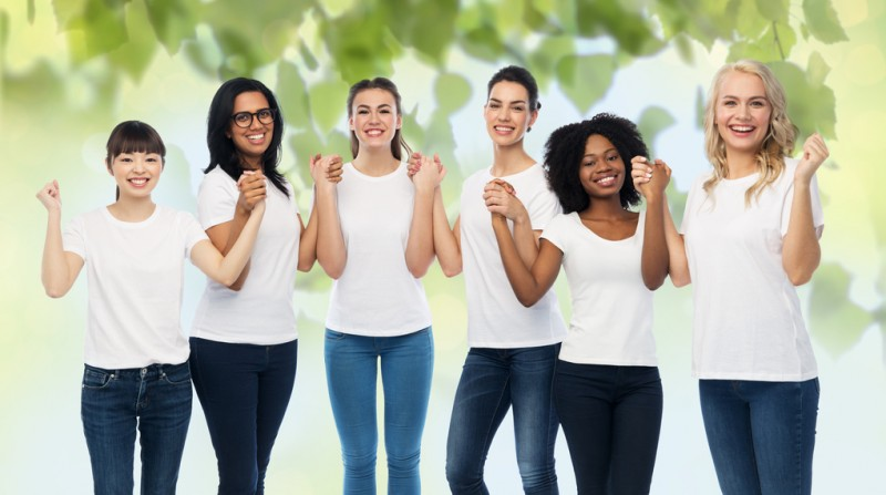 Six diverse, smiling women all wearing white t-shirts and blue jeans stand together hand-in-hand.